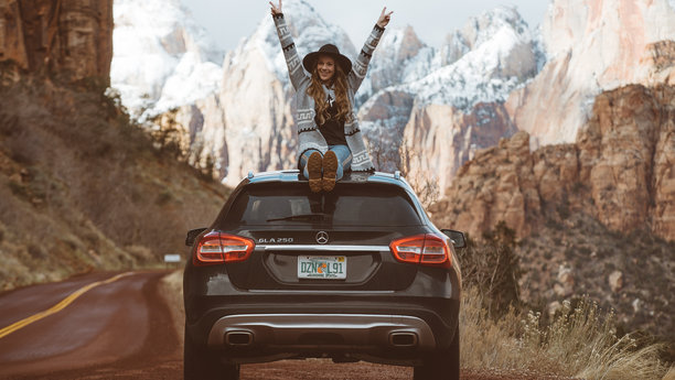 Sixt dívka sedící na střeše BMW
