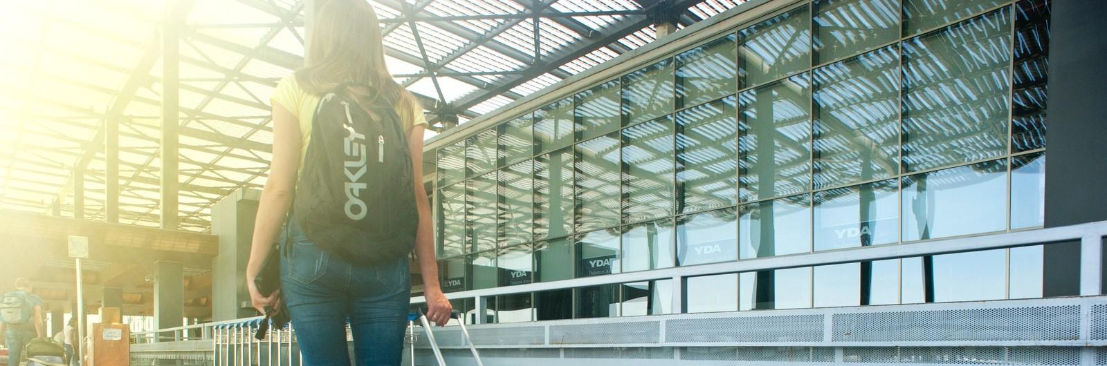 Žena se zavazadly před terminálem letiště