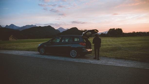 BMW sotevřeným kufrem stojící na kraji silnice