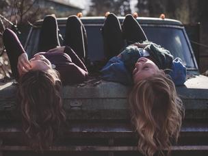 Dívky ležící vedle sebe na kapotě auta